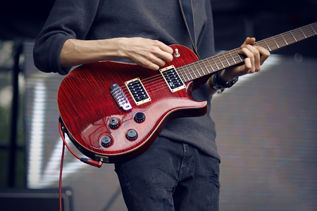 The guitarist, dressed in a gray sweater and dark faded jeans, plays a beautiful red electric guitar while standing on stage during a rock concert.