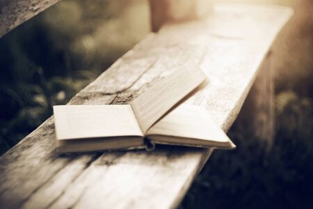 An old open paper book, with the wind turning the pages, lies on a wooden bench cracked by time. Stock Photo