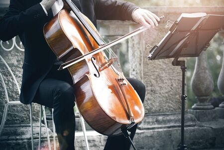 A musician in a classic black suit plays the cello with a bow, sitting on an elegant white chair on a stone terrace and looking at the musical notation.