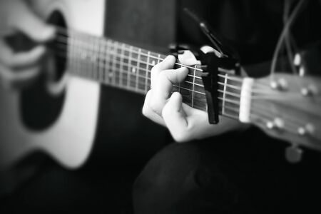 Black and white image, where a person plays a melody on an acoustic six-string guitar, on the fretboard of which the strings are clamped with a capo Stock Photo