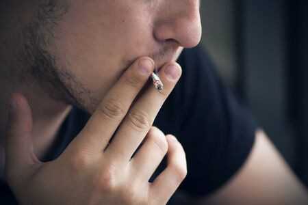 A guy in dark clothes with a stubble on his face is inhaling nicotine from a burning cigarette, holding it with two fingers. Legal harm to health.