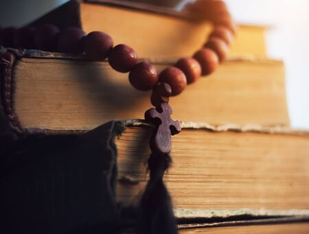 Beautiful rosary of mahogany with a cross lie on the ancient Holy Scriptures, illuminated by sunlight. Holiness and antiquity.