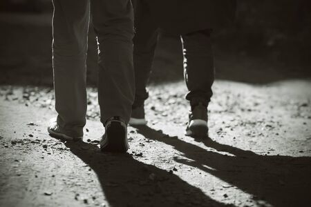 Black-and-white image of the, where its feet two man, dressed in sneakers and trousers, go on foot on sandy-rocky road. People go from light to darkness.