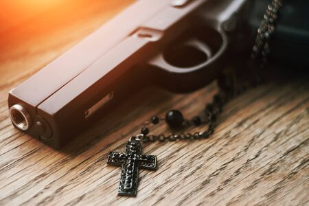 On the old wooden surface is a gun and a rosary with a black cross on a chain, illuminated by sunlight. Holy war or the atonement of sin