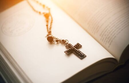 The sacred black Gothic cross on a chain with black beads lies on the pages of an open book, in which the texts and the outline of the pentagram, illuminated by sunlight. Stok Fotoğraf