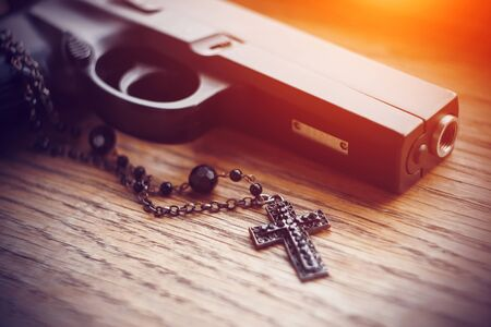 On the old wooden surface lies a black gun and a black cross on a chain with black beads, illuminated by a bright aggressive light.