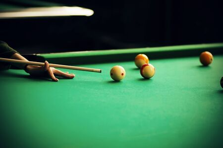 A woman in a green sweater holds a cue and aims at a billiard ball, which is among the other balls on the green billiard table.