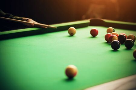 The player helps himself with his hand to aim the cue at the billiard ball lying among the others on the green billiard table Stock fotó