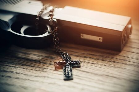 On a wooden table lies a gun lit by sunlight and black carved Holy cross with black beads on the chain.