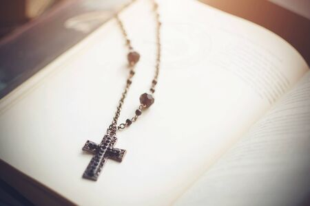 Black metal cross with patterns and beads on a chain lies in an open book with magical texts, illuminated by a pale light. Stok Fotoğraf
