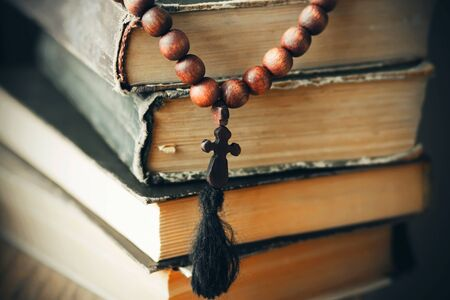 A wooden rosary with a carved cross hangs on a pile of old, time-worn books about sacred truths. Foto de archivo - 129208420
