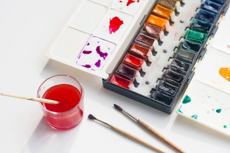 Watercolor palette with a lot of shades, a few fluffy brushes and a glass Cup of water for washing brushes, already stained red.