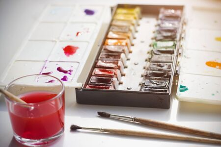 On a white table, illuminated by sunlight, there are watercolor paints in a plastic box, brushes for drawing and a glass with water for washing brushes, which is already painted with paint.