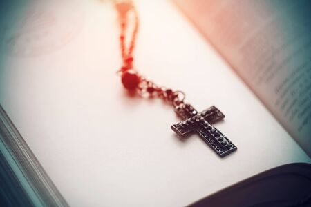 A black Gothic cross with black beads on a chain lies on an open book for black magic and dark rituals.