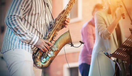 A skilled jazzman plays a Golden saxophone at a concert, creating an accompaniment to the singer. 版權商用圖片