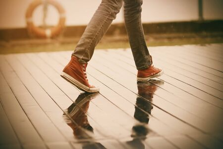 A teenager in red sneakers and regular jeans walks in rainy weather through puddles on a wooden embankment, on the fence of which hangs a red lifeline.