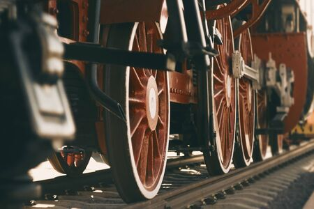 A vintage photo of the red big wheels of an old 20th-century locomotive that stands on rails, illuminated by sunlight.