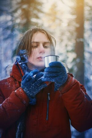 The guy in a red warm jacket and blue gloves froze during a hike through the winter thick pine forest, so drinking from a Cup of hot tea, while Smoking a cigarette.