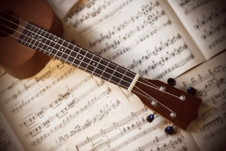 A small four-stringed ukulele with nylon strings lies on old white scattered pages of sheet music.