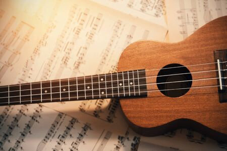 A small wooden ukulele with nylon strings lies on scattered sheets of musical notes, illuminated by the light