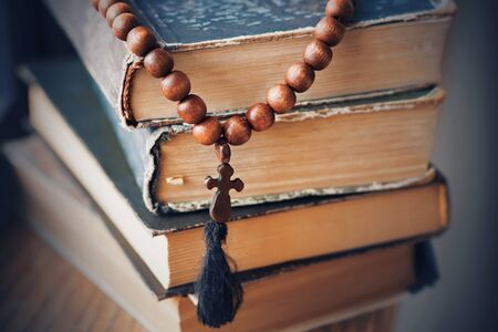 The sacred rosary, made of mahogany, lies on a pile of old battered books in which religious precepts are written. 版權商用圖片