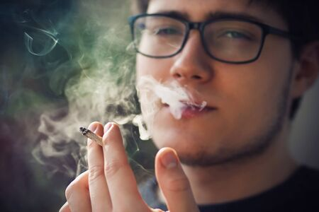 A young handsome guy in glasses smokes a cigarette and exhales smoke, which is illuminated by sunlight, getting untold pleasure from it.