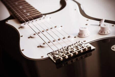 Black and white beautiful elegant electric guitar with six strings for the performance of musical works.