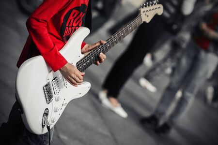 A young street musician in a red t-shirt plays rock music on a white electric guitar, standing in the middle of a crowded street. Фото со стока - 133271872