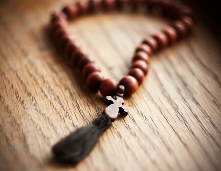 A sacred rosary in mahogany with a carved cross lies on a wooden table, illuminated by daylight.