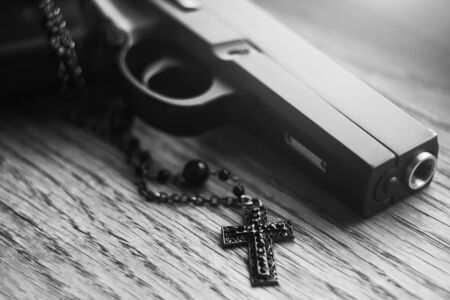 A black-and-white image of a gun that lies on a wooden surface along with a black Catholic cross, embodying war and religion. Reklamní fotografie