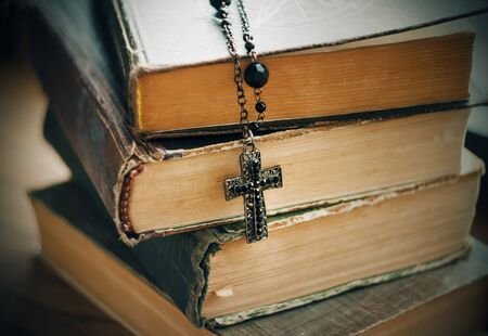 Old battered thick books on magic and rituals and a black Gothic cross on a chain.