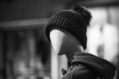 A black-and-white image of a sinister, frightening, faceless mannequin standing in a clothing store wearing a hat and hoodie.