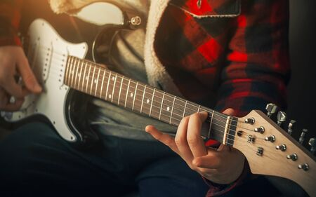 A guitarist in a checked red and black jacket plays an impromptu rock tune on a black and white electric guitar, illuminated by sunlight. Фото со стока - 135188159