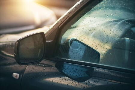 The rain-soaked windows and mirrors of the car, which are illuminated by the light of the sun that has just come out from behind the clouds.