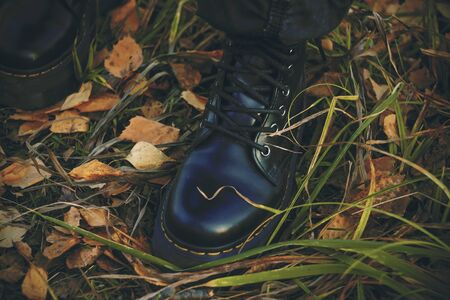 Womens feet in severe black shoes stand on the long green grass with fallen into it yellowed birch leaves in the autumn season.
