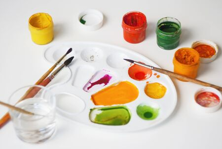 The artist's workplace on a white table, on which there are gouache paints of different colors, a plastic white palette and a glass of water to dilute the paint.