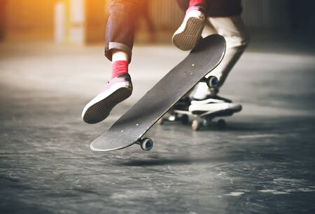 Jump of a teenager in jeans, pink socks and sneakers on a skateboard illuminated by a bright orange light. Stok Fotoğraf