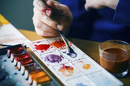 The artist's paint-stained hand holds a paint brush and mixes with watercolor blue paint on the palette, and next to it is a glass of dirty water in which the paint brushes were washed.