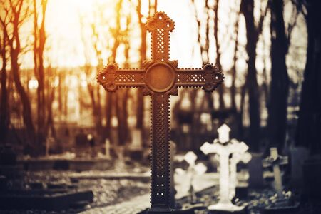 A beautiful old rusty cross stands in a large dark cemetery against a background of white crosses and tree trunks, illuminated by bright sunlight.