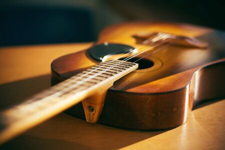 On a wooden table lies an old acoustic guitar that lacks strings and is illuminated by bright sunlight.