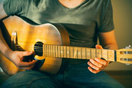 A young musician in a green t-shirt and blue jeans plays an old, dilapidated acoustic guitar that lacks a string.
