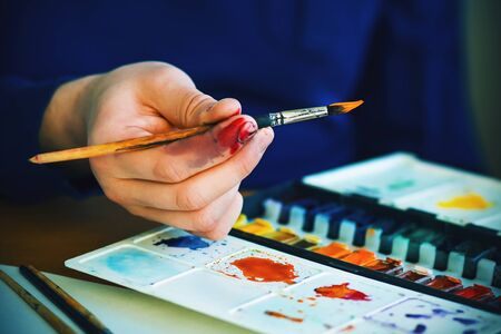The artist holds in his hand an elegant brush with orange watercolor paint on the end and is going to draw with it. And next to it is a palette with a wide variety of shades. Stock fotó