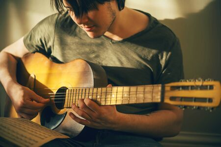 A young musician with long bangs and stubble on his face in a green t-shirt plays a tune on an old battered guitar, consulting the notes on a sheet of paper that lies on his knee. Standard-Bild