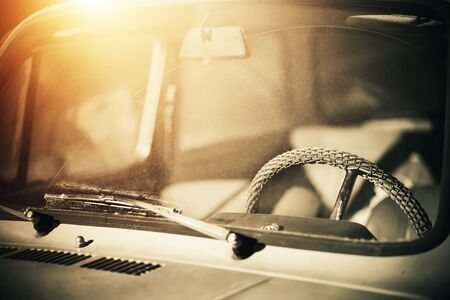 Through the dirty windshield, you can see the interior of an old retro car with a wicker steering wheel, which is illuminated by bright sunlight.