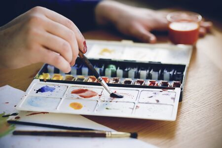 The artist holds a brush in his hand, which mixes colors on a plastic palette with watercolors that lie on a wooden table next to art supplies. 스톡 콘텐츠