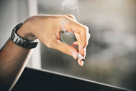 An elegant man's hand, which is wearing a wrist watch, holds a cigarette that emits toxic nicotine smoke.