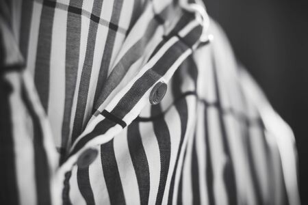 Black and white image of a striped loose soft cotton shirt buttoned up.