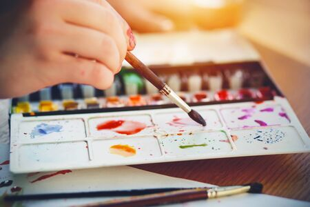 The artist draws with a brush and watercolors of different colors