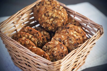 A pile of homemade oatmeal cookies with cereals is in a square wicker basket on a white towel on a gray table.