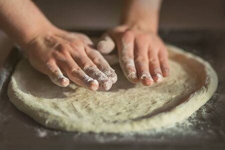 The cook rolls out the dough for homemade delicious pizza on a dark baking tray, sprinkled with flour. Home cooking.